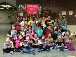 Elementary students pose for photo and hold donated bags