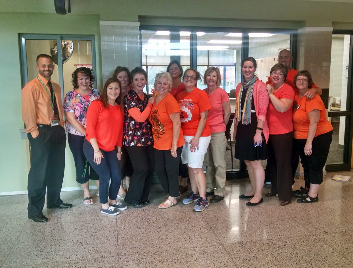 Staff pose in the hallway wearing orange shirts