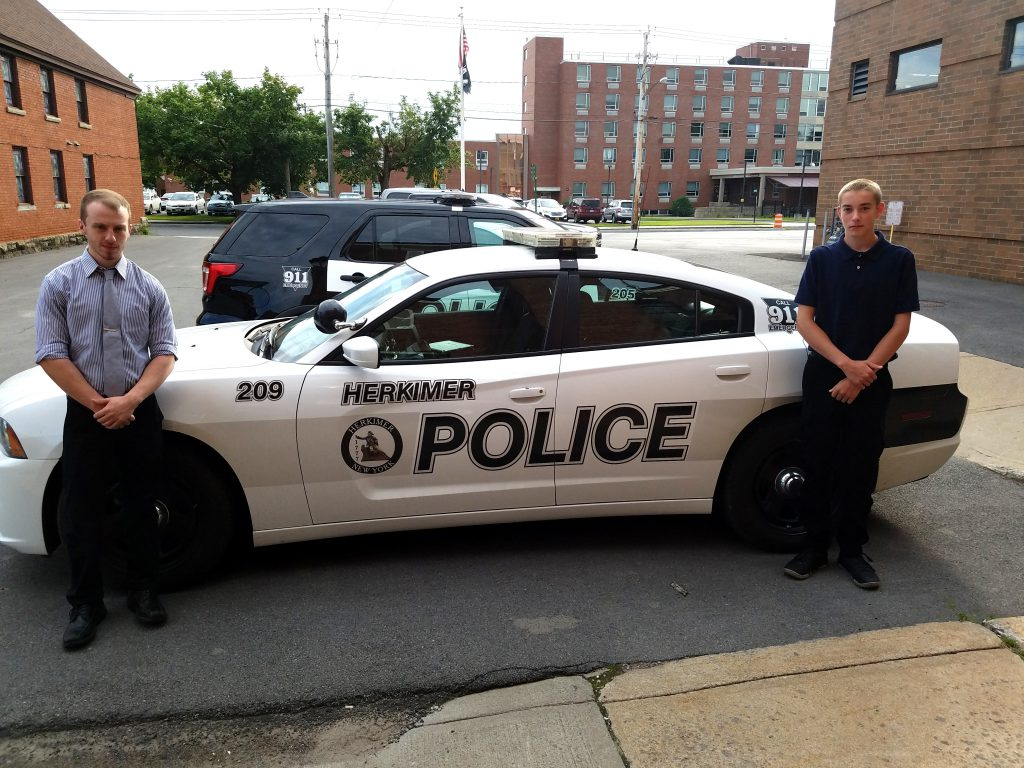 Two young men stand next to a police car