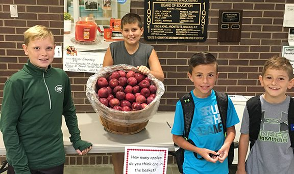 Four boys stand near a large basket holding apples