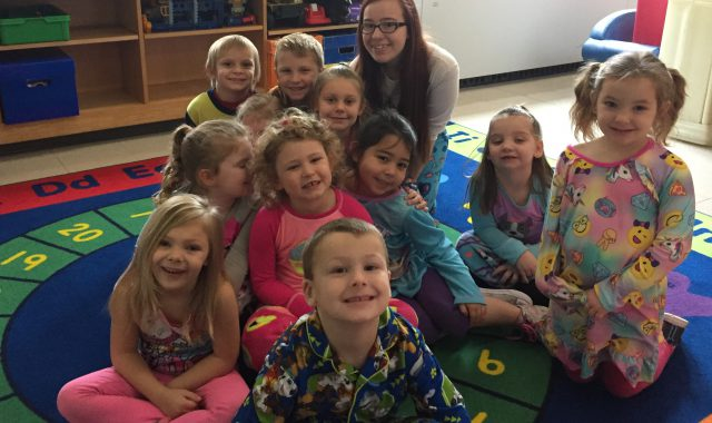 Students wearing pajamas pose with their teacher