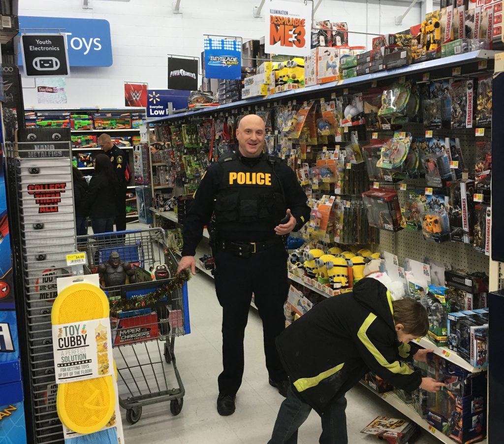 Police officer looks on as child selects toy from shelf