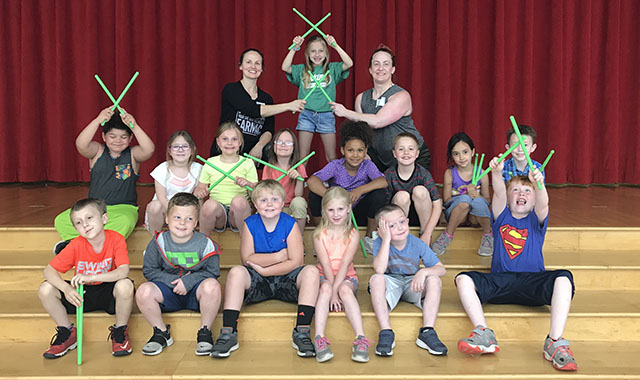 Elementary students pose with light sabers
