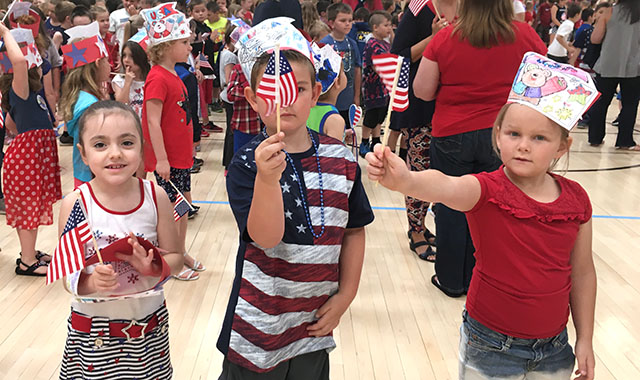 children hold up American flags