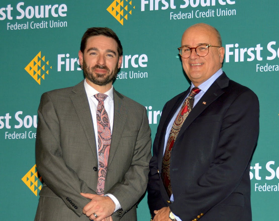 Two men pose in front of a backdrop that reads First Source Credit Union