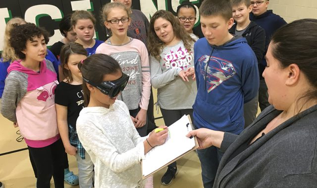 One student is blindfolded while others look on