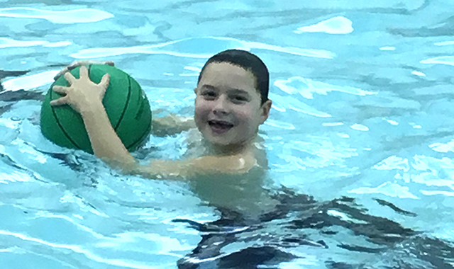Student smiles while swimming and holding a green ball