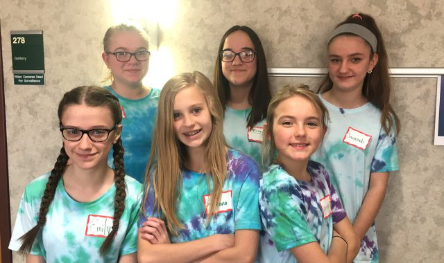 Six students pose for photo wearing tie-dyed T-shirts