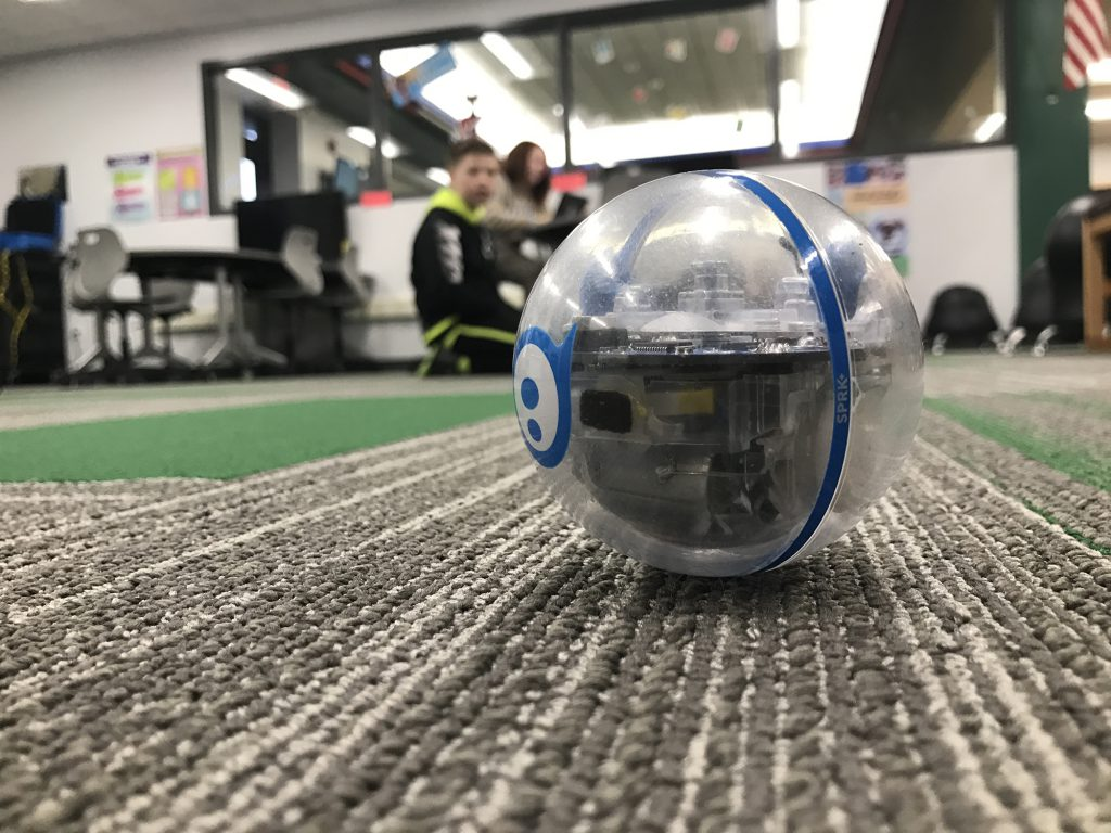 Small spherical robot is seen at close range on the carpet of a classroom