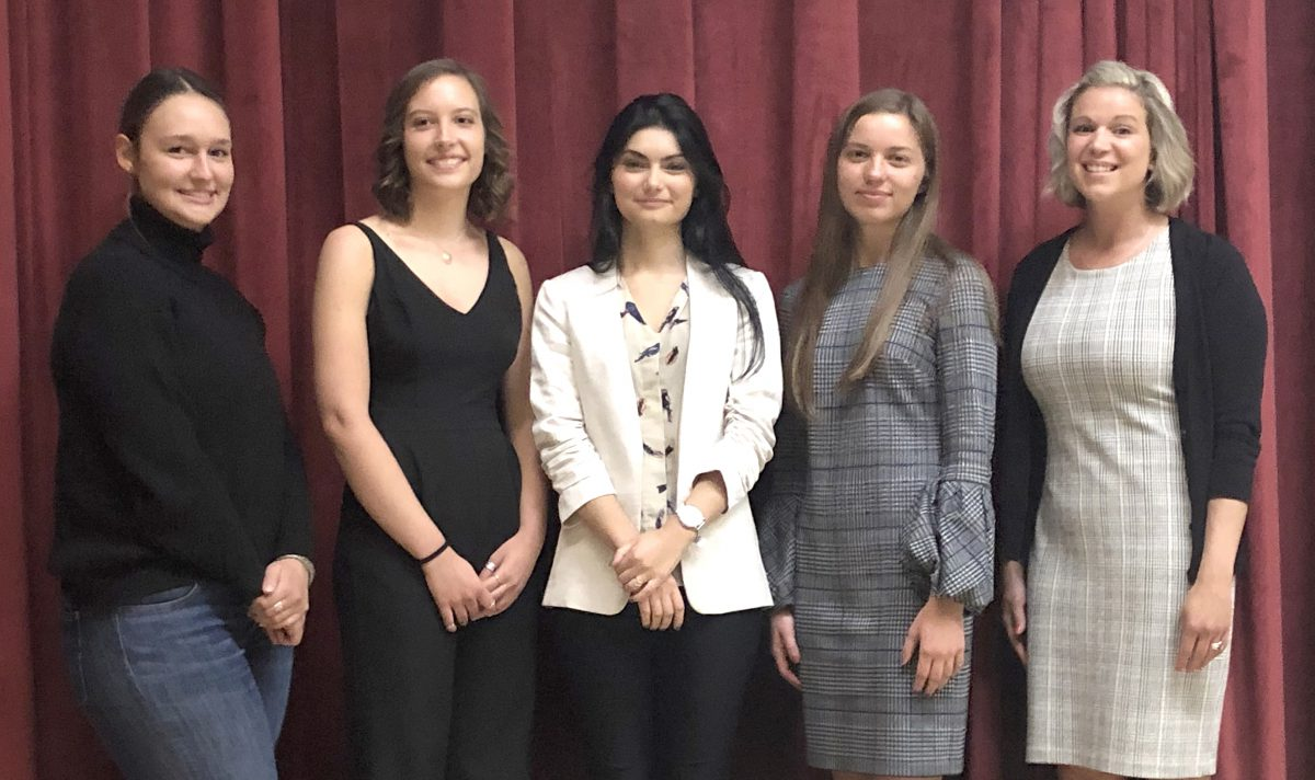 Four students and a guidance counselor stand in front of a red curtain