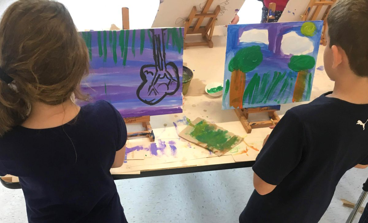 Two students paint on small easels