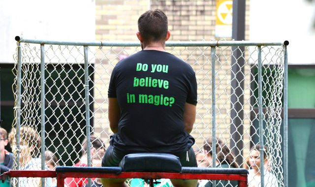 """Man seated in dunk tanks wears T-shirt that reads """"Do you believe in magic?"""""""