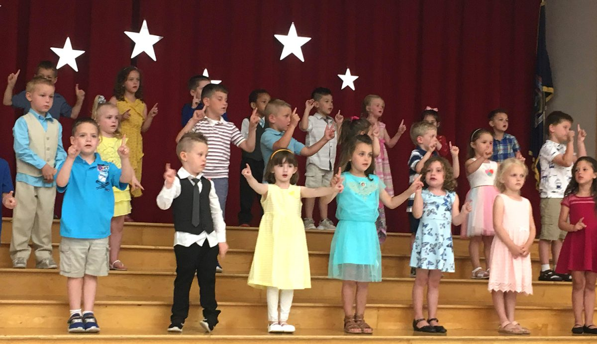 Students pose on the steps of a stage decorated with stars