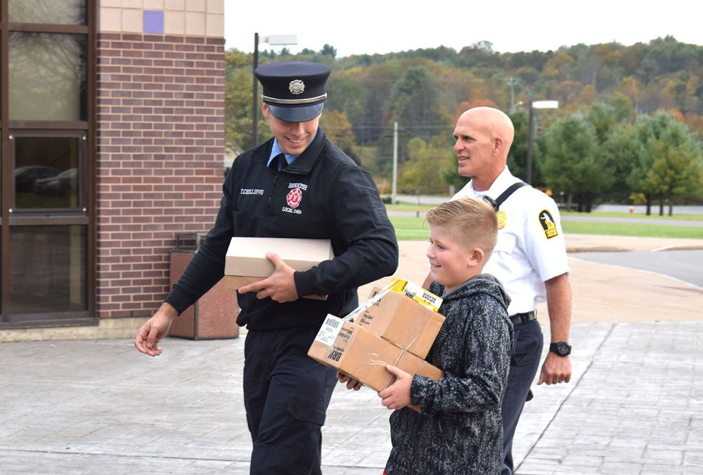 Firefighters and a student carry boxes