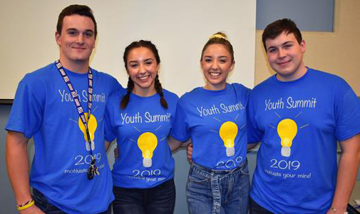 Four students wearing Youth Summit shirts