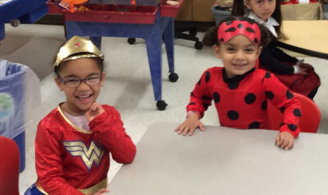 Students wearing Halloween costumes sit in classroom