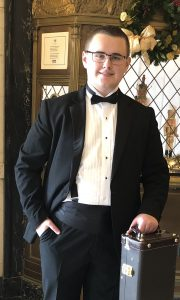 Student in tuxedo with instrument case