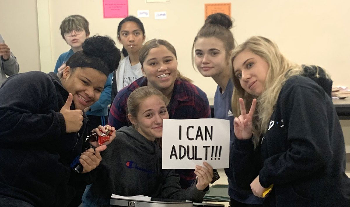 Students hold sign that reads, 'I can adult!'