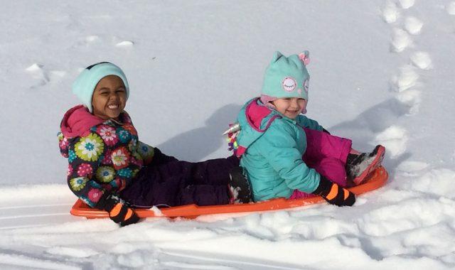 Two children sledding