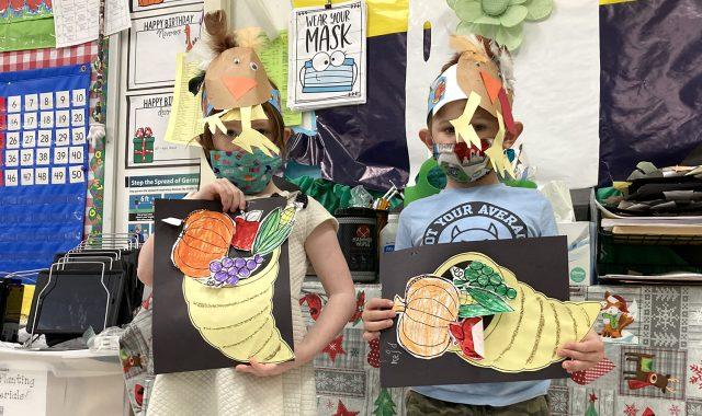 Students hold up paper cornucopias
