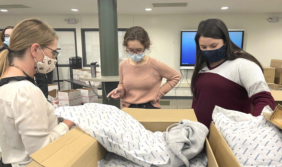 Students wearing masks look at a box