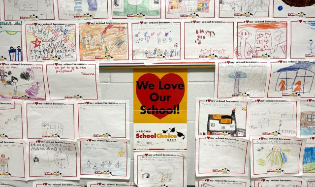 """A sign that reads """"We love our school"""" is surrounded by children's drawings"""