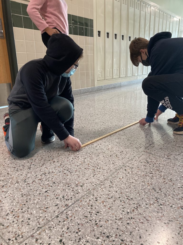 Two students sit in a hallway and measure distance with a ruler