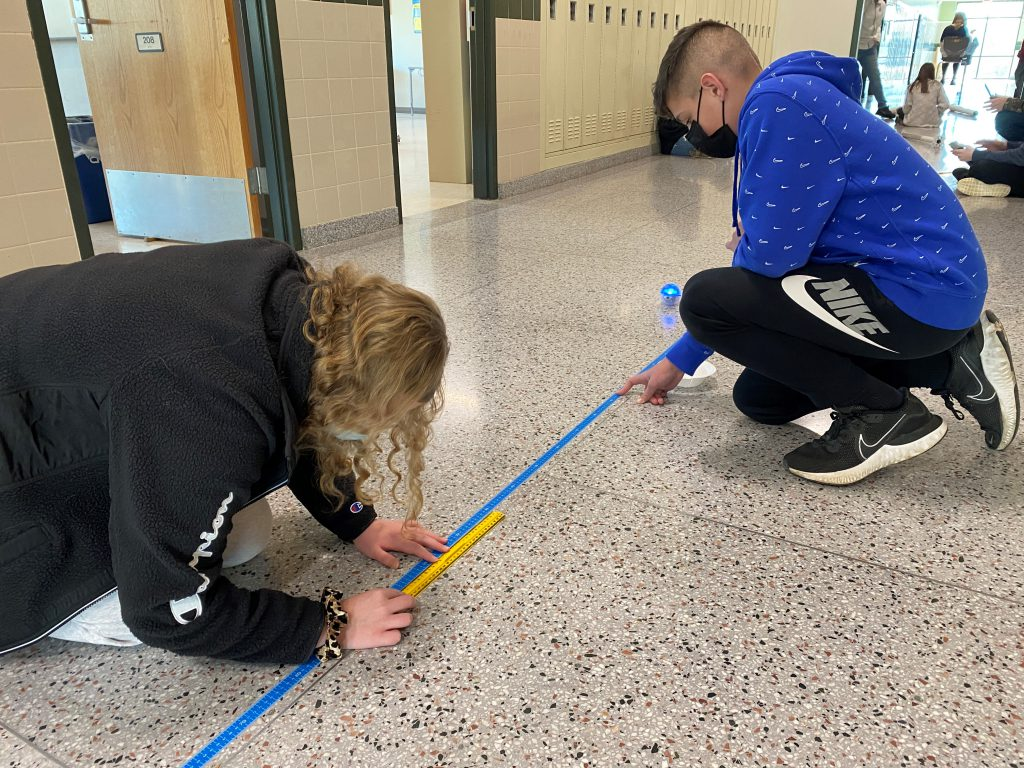 Two students sit in a hallway and measure distance with a ruler.