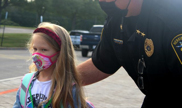 A student stands with a police officer