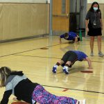 Students in the gym do push ups