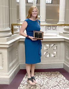 Heather McCutcheon holds a plaque