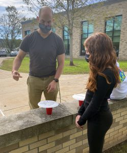 A student and teacher work on a project outside