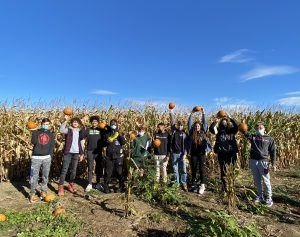 Students hold their pumpkins for the camera